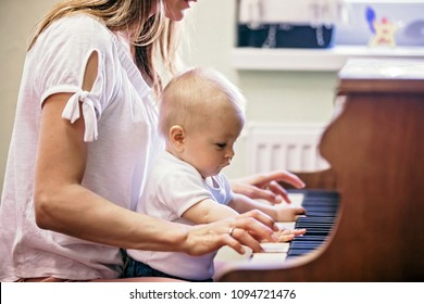 Mother and toddler baby boy, playing piano at home, child learning