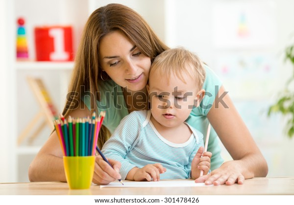 Mother and toddler child drawing and painting together