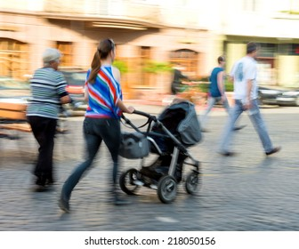 Mother with toddler child in the stroller in motion blur
