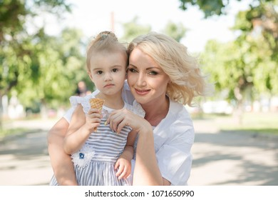 Mother and toddler daughter in the city posing eating ice cream. Deadpan photography.