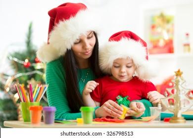 Mother and toddler little girl preparing Christmas decor.