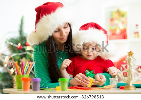 Mother and toddler little girl preparing Christmas decor.