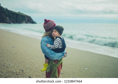 A mother and toddler are relaxing on the beach in the autumn