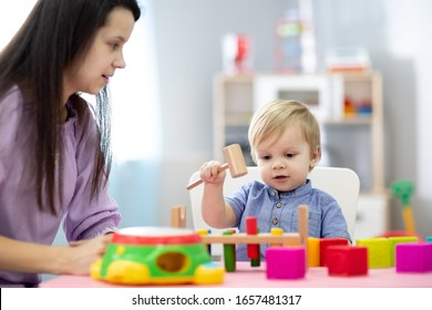 Mother and toddler son play with educational toys together at home