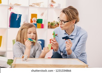Mother with toys playing with daughter with Asperger's syndrome at home