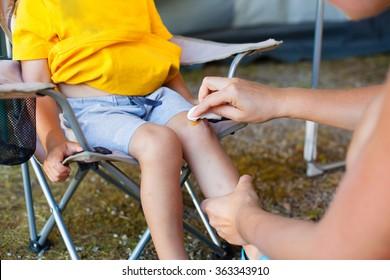 Mother treats her son skinned knee (Shallow DOF).