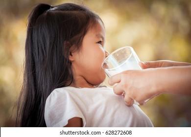 Mother try to give a glass of milk to asian little girl she don't like it