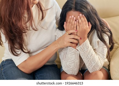 Mother trying to comfort her daughter covering face with hands and crying after being bullied in school