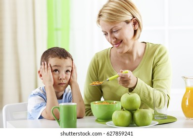 Mother trying to feed her son.