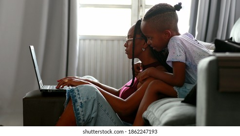 Mother trying to work in front of laptop with little boy son wanting attention, parent working from home