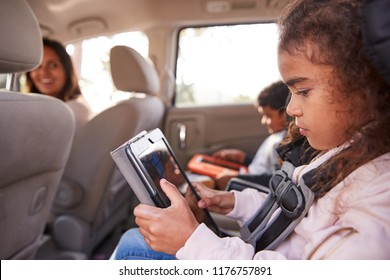Mother turns around to kids using tablets in the back of car