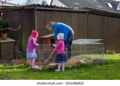 mother and twin daughters cleaning the rabbit hutch in the backyard