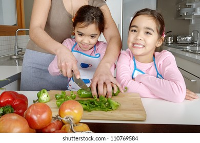 Mother and twin daughters learning to chop vegetables together in the kitchen, using a chopping board and surrounded by fruit and vegetables.