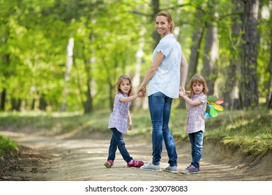 Mother with twin girls walking in forest