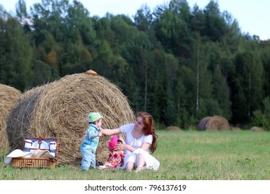 mother with twins in field in a summer day