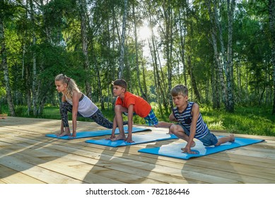 Mother and two boys doing stretching exercises in park on a sunny day