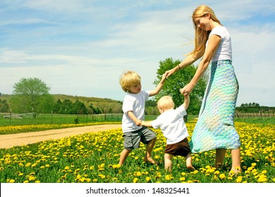 Mother and two children, a baby and a small child  holding hands and dancing and playing outside in a field of Flowers.