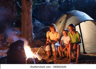 Mother with two children at the camping at night