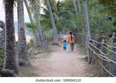 A mother, two children and a dog on Don Khon island walking among the palm trees at the beach