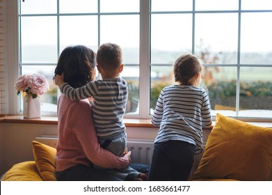 mother and two children looking through window at quarantine time