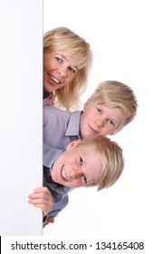 Mother with two children looks around a white wall