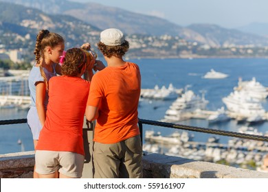 mother with two children on observation deck of palace Grimaldi, woman looks through binoculars