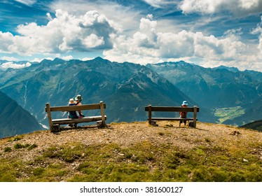 mother with two children resting on bench with mountain view during hiking in austrian alps near kaprun in salzburg