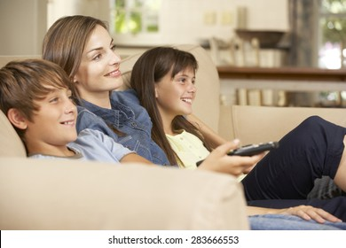 Mother And Two Children Sitting On Sofa At Home Watching TV Together