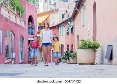 Mother and two children, walking hand in hand on a colorful street in France village Villefrance