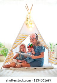 Mother and two  cute girl playing and reading together indoors