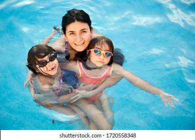 Mother and two cute little girls holding together in the blue water of a swimming pool, on a beautiful spring sunny day.