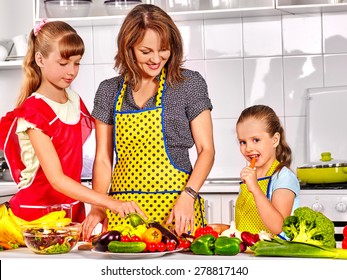Mother and two daughters cooking at kitchen.