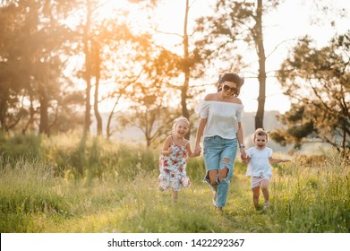 Mother and two daughters having fun in the park. Happiness and harmony in family life. Beauty nature scene with family outdoor lifestyle.