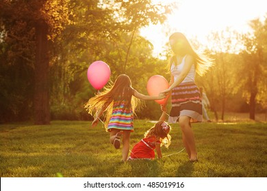 Mother and two daughters holding hands circling. Family time together. Cheerful picnic. Girls with balloons. Soft focus