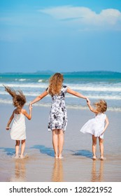 mother and two daughters jumping on the beach