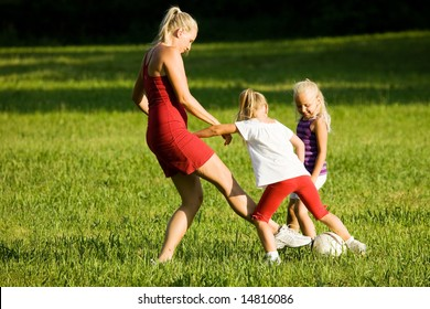 Mother with two daughters playing football (well, soccer for North America) on a green, sunlit meadow