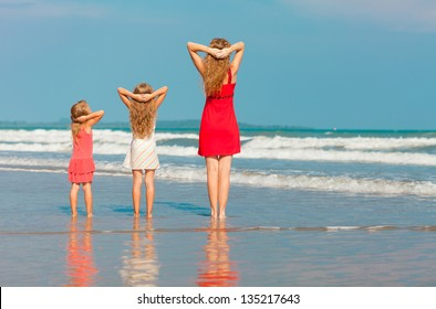 mother and two daughters standing on the beach