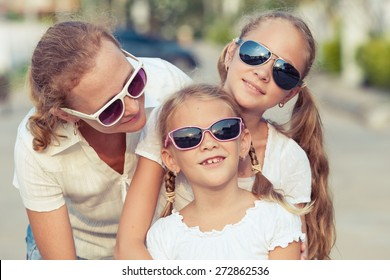 Mother and two daughters standing on the road at the day time. Concept of friendly family.