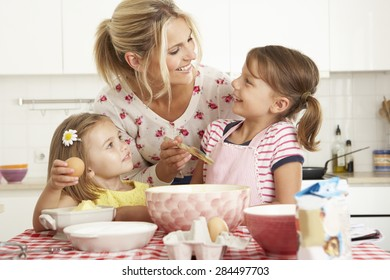 Mother And Two Girls Baking In Kitchen