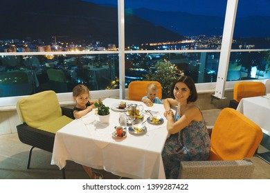 mother and two kids at cage with night city view