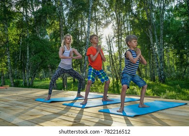 Mother and two kids doing yoga outdoors in nature
