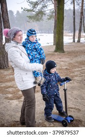 Mother and two kids having fun outdoors. Walking winter forest first snow.