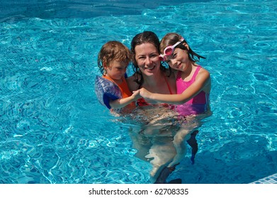Mother with two kids having fun in swimming pool