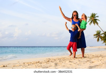 mother and two kids playing on the beach