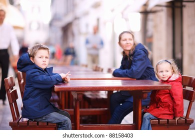 Mother and two kids relaxing at empty street restaurant on autumn day