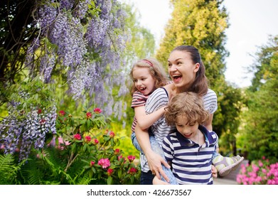 Mother and two kids relaxing in the park. They are having a great holiday. Seven surround flowering shrubs and green plants. The benefits to health and soul