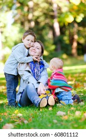 Mother and two kids sitting on grass at sunny autumn day