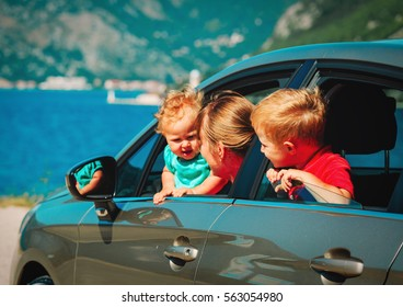mother with two kids travel by car on sea vacation
