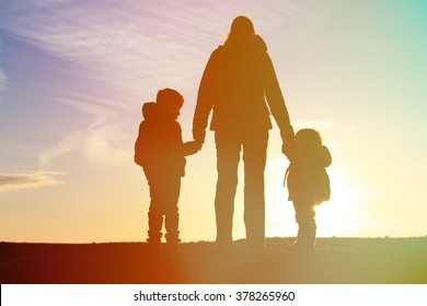 mother and two kids travel at sunset
