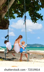 Mother with two kids at tropical white sand beach